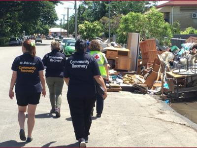 Community recovery workers walking down street with flood debris