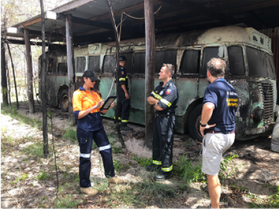 Workers standing in front of burnt out bus