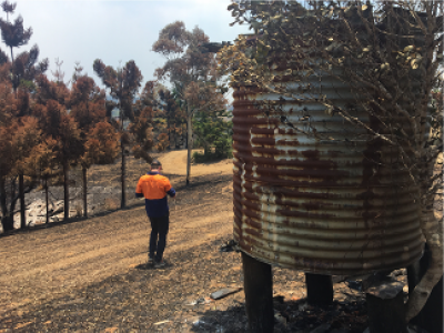 Worker standing near burnt out water tank