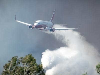 Plane dropping water over bushfire