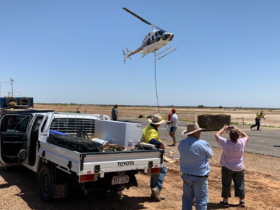 Helicopter dropping fodder in outback with people watching on