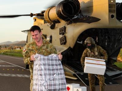 Army personnel unloading supplies from helicopter