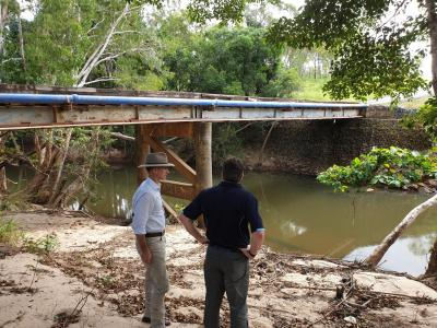 Two people viewing damage next to bridge