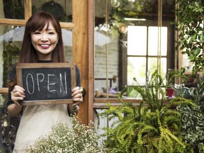 Smiling woman holding sign that reads 'open'